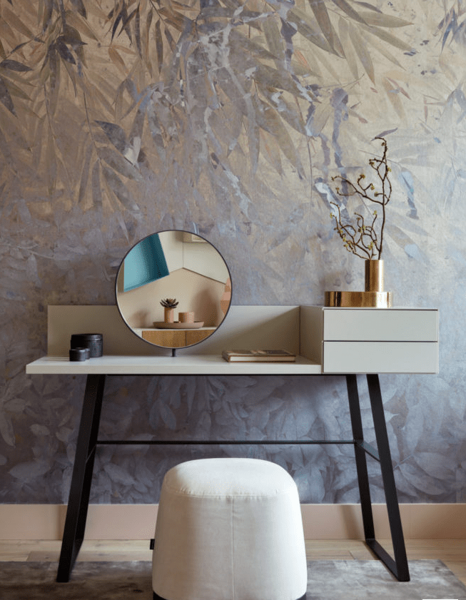 a modern makeup nook with a stylish vanity,a round mirror, a white pouf as a seat is lovely and chic