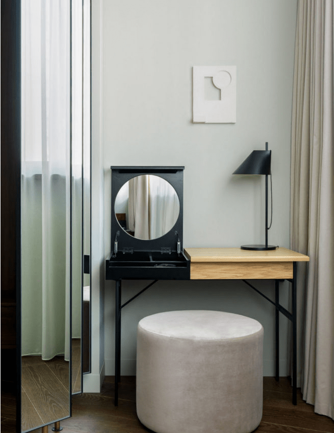 a modern makeup nook with a vanity with storage, a hidden mirror, a black lamp and a round pouf as a seat