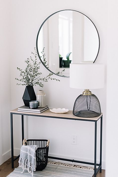 a modern monochromatic entryway with a narrow console, a round mirror, a cool lamp and some vases