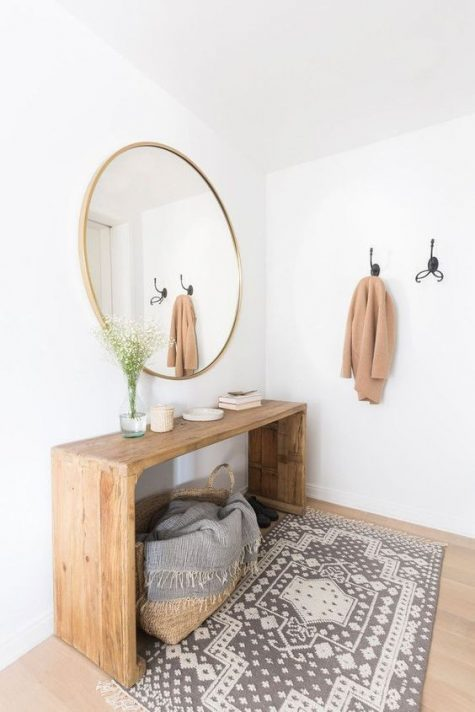 a modern warm-colored entry with a wooden bench, a round mirror, a printed rug and a basket with a blanket