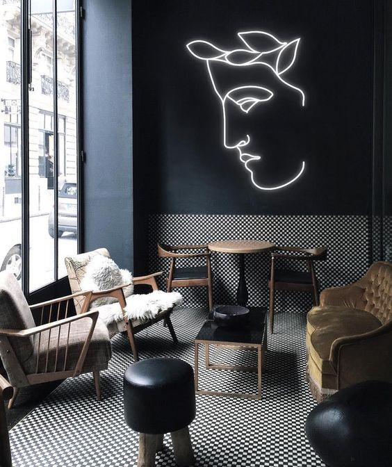 a moody and refined mid-century modern living room in black and white, with a neon light on the wall for a lighter and airier feel