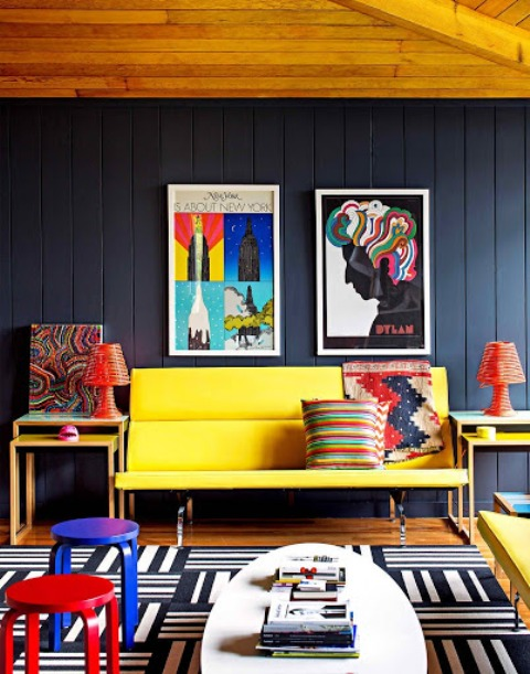 a moody living room with black walls, a yellow sofa, colorful stools and bold artworks is amazing