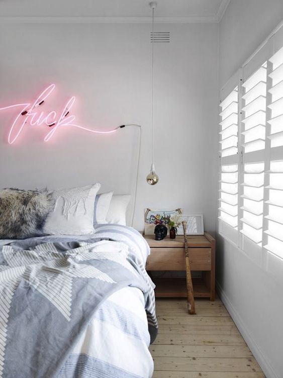 a neutral and airy bedroom with a fun pink neon sign that creates a mood and adds a fun touch to the space