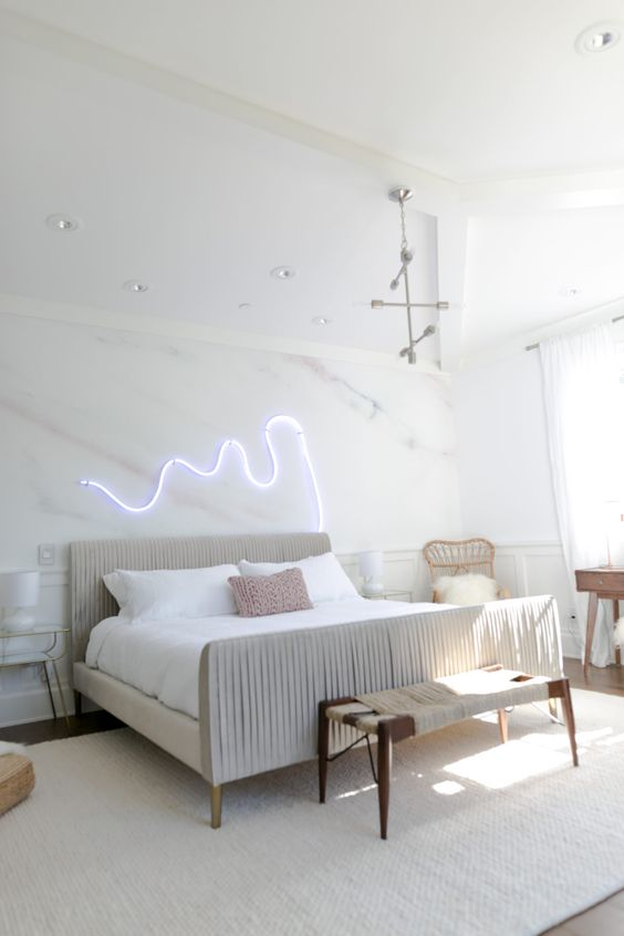 a neutral and chic bedroom with an upholstered bed, wooden furniture, some lights and a chandelier and a neon light