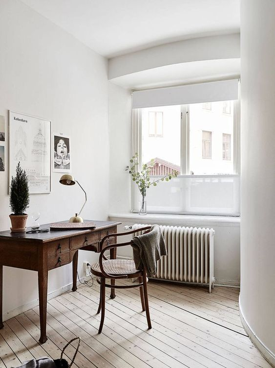 a neutral home office wiht a dark stained wooden desk, a rattan chair, a monochromatic gallery wall and much natural light