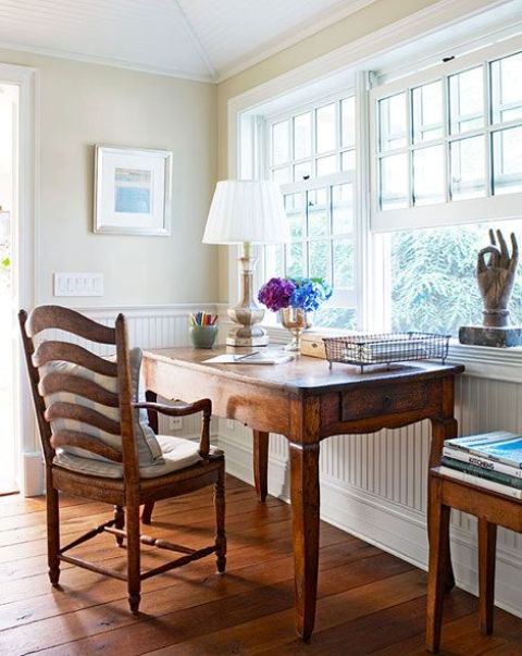 a neutral home office with panels, a stained wooden desk, a stained chair, a table lamp and some decor is welcoming