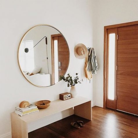 a peaceful modern entryway with a sleek bench, a round mirror, a bowl and greenery in a vase