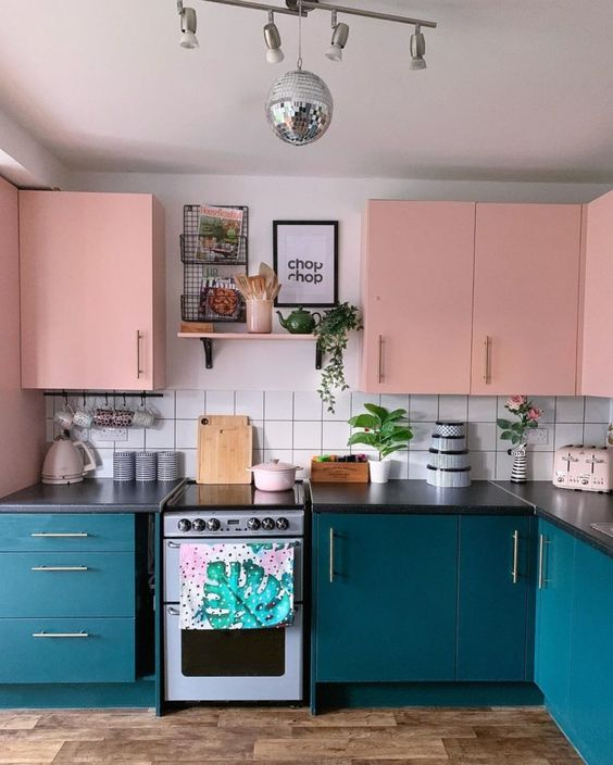 a pretty colorful kitchen with navy and pink cabinetry, a white square tile backsplash plus a silver chandelier with a disco ball