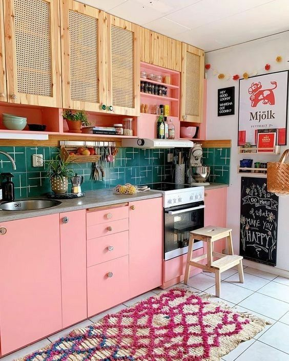 a pretty kitchen with pink lower cabinets and rattan upper ones, a green printed tile backsplash and a bold rug is very welcoming