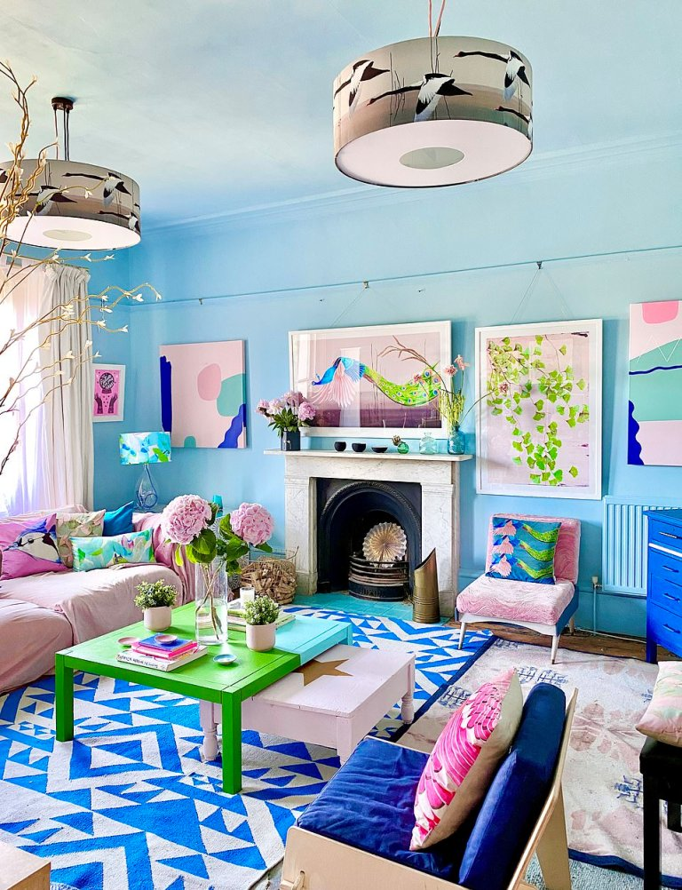 a pretty living room with light blue walls, a pink sofa and a chair, a navy one, a fireplace clad with stone, bold artworks and pillows