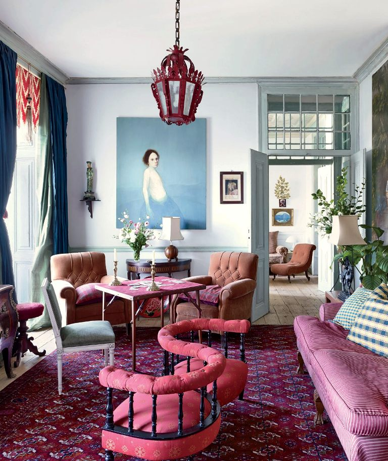 a refined and colorful living room with vintage red, coral and green furniture, a bold printed carpet, navy and green curtains and a red lantern