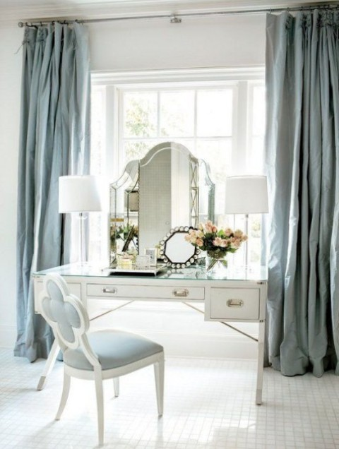 a refined beauty space with a white art deco vanity, a powder blue chair and a couple of lamps and mirrors and much natural light