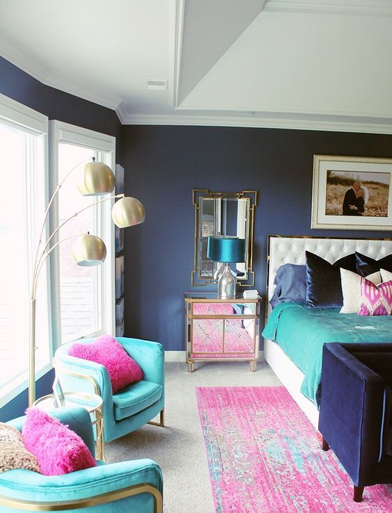 a refined colorful bedroom with navy walls, turquoise chairs, pink pillows and a rug, bold bedding and shiny mirror and metallic touches