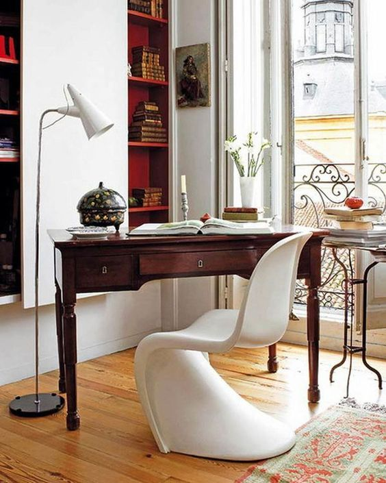 a refined contemporary home office with built-in bookshelves, a vintage stained desk, a white sculptural chair and a small table