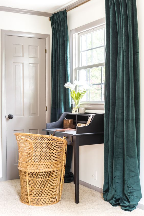 a refined home office nook with a graphite grey writing desk, a rattan chair for a more modern feel, teal curtains