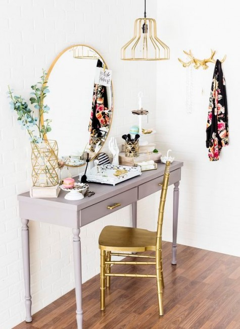 a refined makeup nook with a vintage grey vanity, a gilded chair, lamp and mirror and a geometric vase is glam and cool