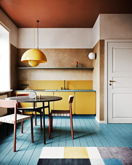 a refined modern bright kitchen with a blue floor, a yellow cabinets, a yellow backsplash and a pendant lamp
