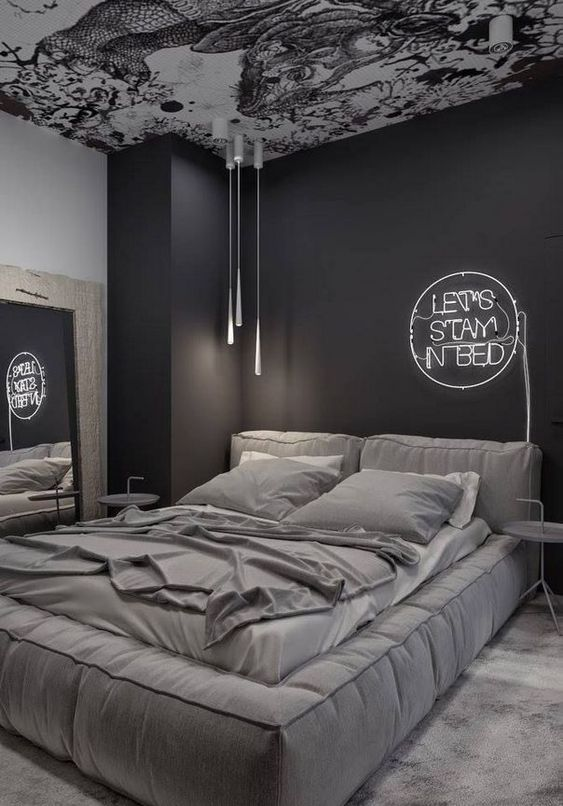a refined moody bedroom with black and white walls, a patterned ceiling, a large upholstered bed and a neon light over it
