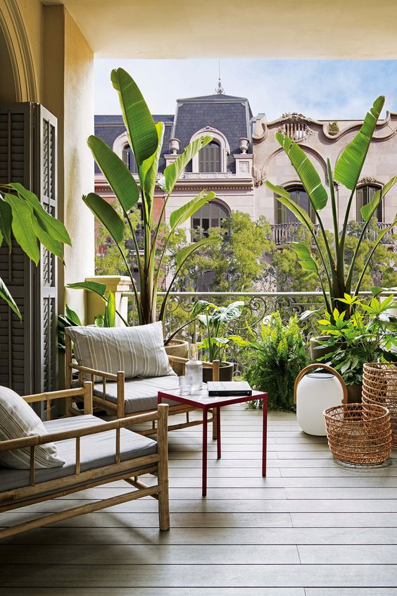 a relaxed balcony with rattan furniture, candle lanterns and potted plants all over the space for a natural feel