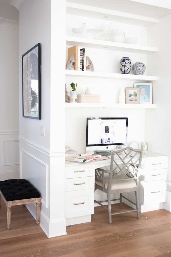 a separate nook for working with built-in shelves and a desk, a cool chair right in the kitchen matching its cabinets