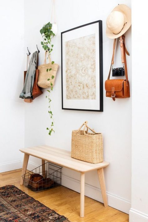 a simple modern entry with a wooden bench, a statement artwork, a wire basket and clothes hangers
