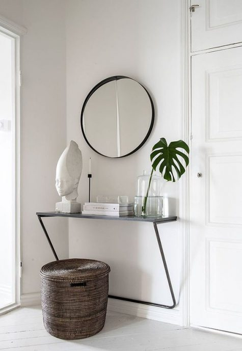 a simple modern entryway with a floating console, a round mirror, a basket for storage and a vase