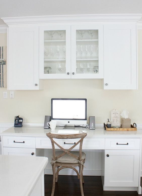 a simple white kitchen with shaker style cabinets, a deskand cabinets, a vintage wooden desk and warm-colored walls