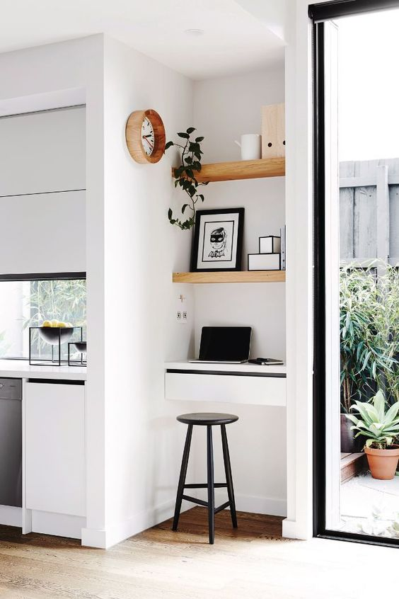 a sleek white kitchen with a window backsplash and a tiny workspace nook with built in shelves and a small desk plus a stool is great