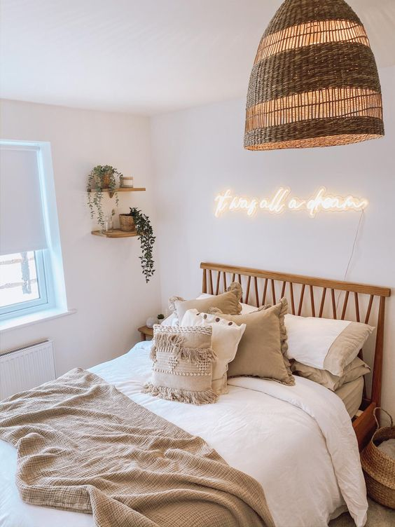 a small and cozy boho living room with a rattan pendant lamp, a neon light for a modern feel and cool pillows