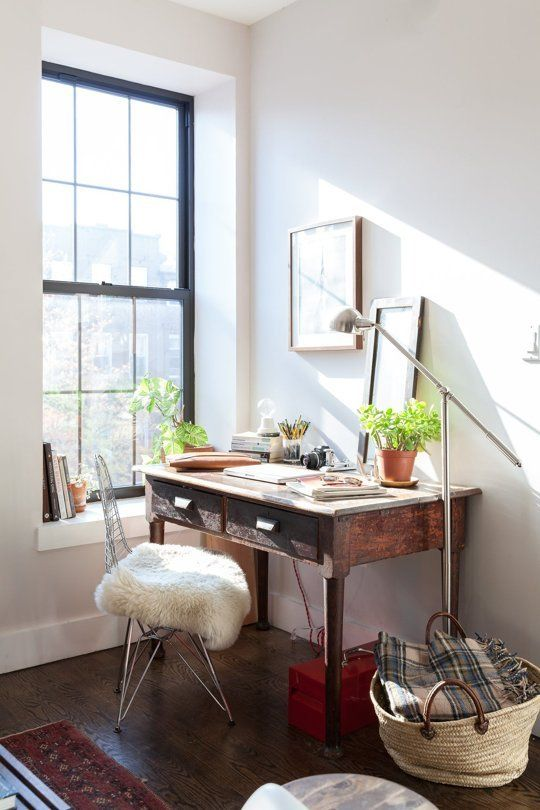 a small and cozy workspace with a dark stained desk, a metal chair, potted plants and pretty artworks plus a floor lamp