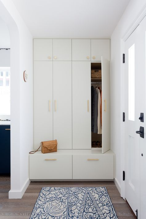 a small and elegant entryway with a creamy built in storage unit with gold handles is very practical