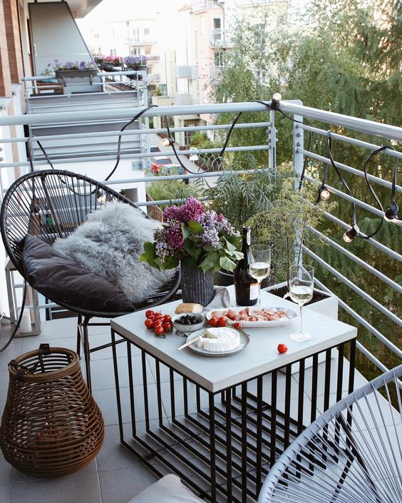 a small and lovely summer balcony with a couple of chairs, a lovely coffee table, a rattan candle lantern and some plants