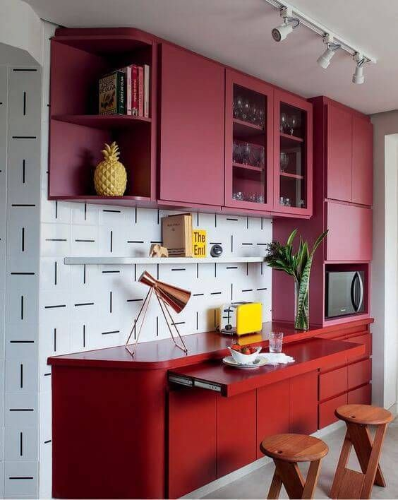 a small bright kitchen with pink and red sleek cabinetry, a black and white tile backsplash and wooden stools