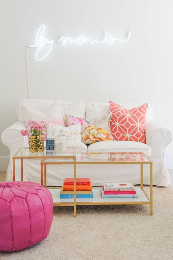 a small glam living room with a white neon sign and a hot pink pouf that add fun and a cool and whimsy touch to the space