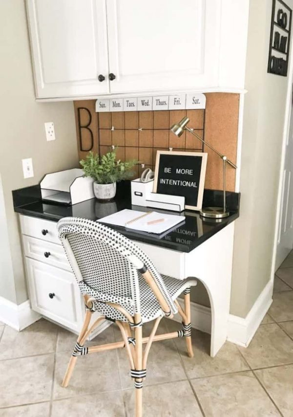 a small home office nook in the kitchen with a desk and a cabinet in the same style, a black countertop, a corkboard and a grid as a schedule