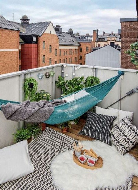 a small summer balcony with a blue hammock, some cushions and pillows, a faux fur throw and potted greenery