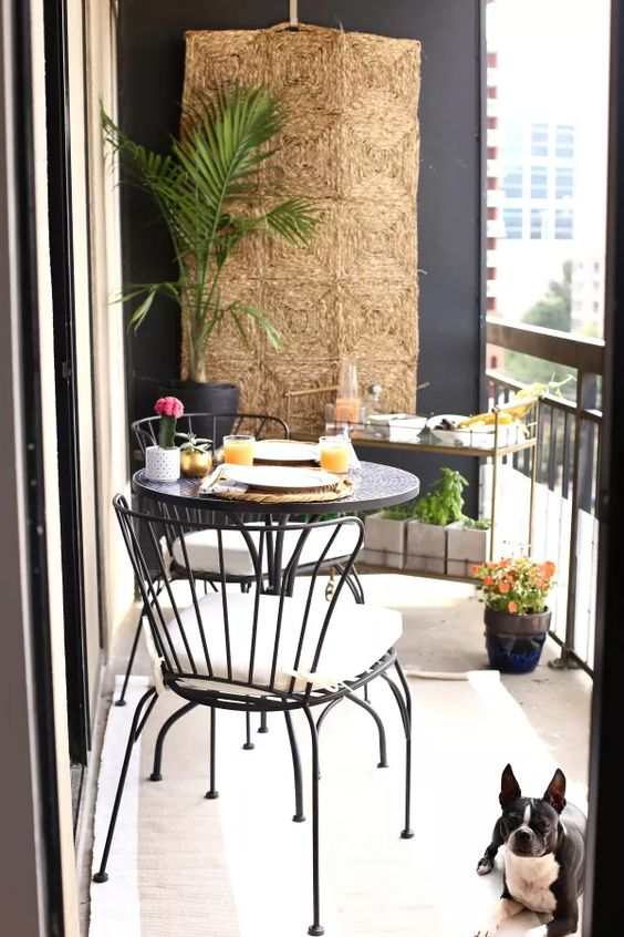 a small summer balcony with a woven hanging, small metal furniture, a cart with drinks and potted plants and blooms