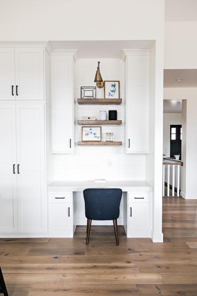 a small workspace in the kitchen with a desk and cabinets that match white kitchen cabinetry, floating shelves and a navy chair