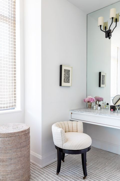 a small yet chic beauty nook with a built in vanity, a large mirror with sconces, a rounded chair and an artwork
