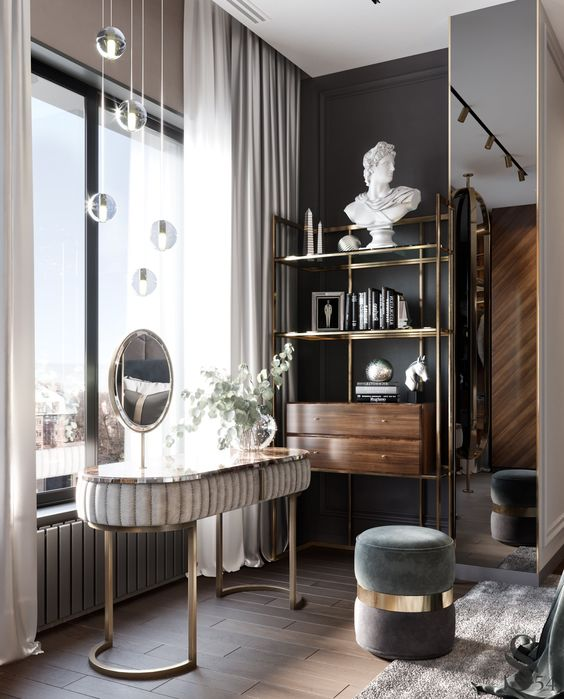 a sophisticated beauty nook with a curved vanity, a round mirror, a grey pouf and pendant lamps over the space
