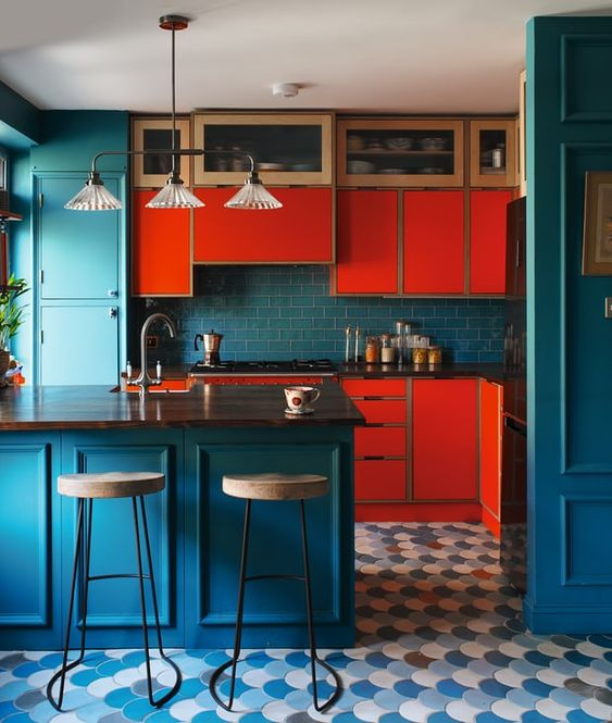 a statement kitchen with blue and red cabinetry, with a blue subway tile backsplash, a blue kitchen island and a vintage chandelier
