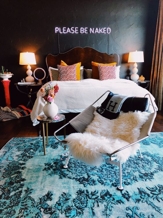 a stylish bedroom with a black accent wall and a neon sign, printed pillows, bold textiles and a blue rug