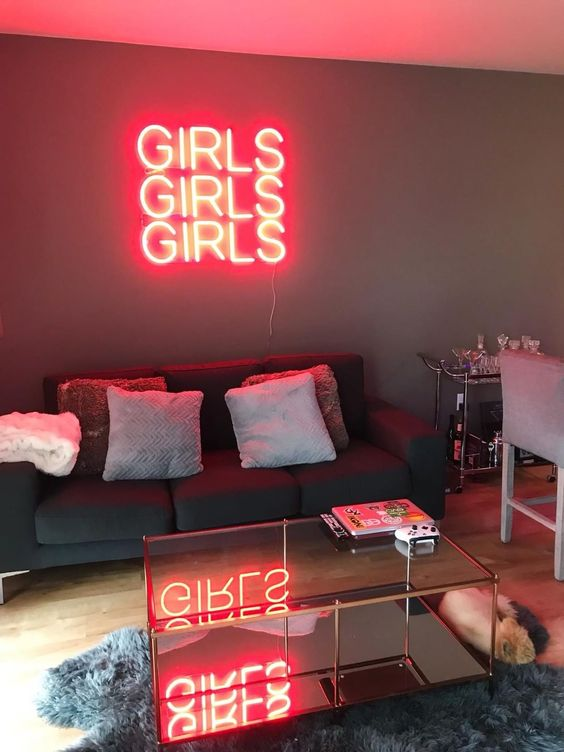 a stylish contemporary living room made bolder and cooler with a red GIRLS neon sign over the sofa