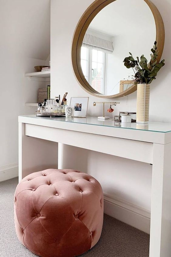 a stylish contemporary makeup space with a white vanity, a pink tufted pouf, a round mirror and some greenery in a vase