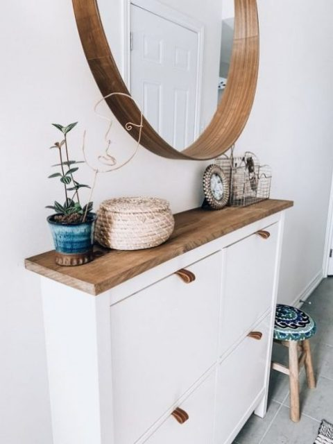 a stylish modern entry with an IKEA shoe cabinet hacked, a round mirror and a potted plant plus a colorful stool