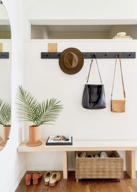 a stylish modern entryway with a sleek bench, a clothes rack, a storage box and a mirror on the wall