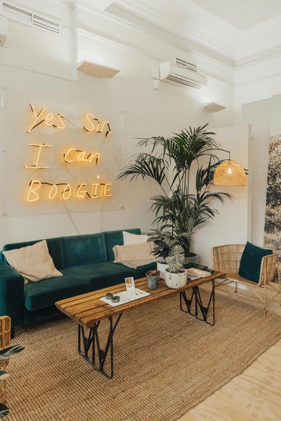 a stylish modern living room with a tropical feel, potted plants and a yellow neon sign as a fun touch to the space