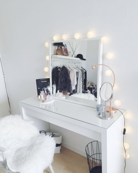 a stylish modern makeup nook with a glass top vanity, a lit up mirror and a faux fur chair is very comfy in using