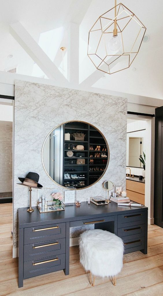 a stylish modern makeup space with a grey vanity or a desk, a faux fur pouf, a large round mirror and some additional smaller ones