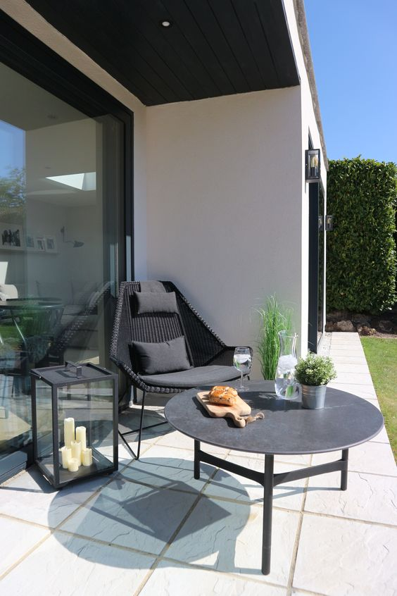 a stylish relax corner with a black woven chair, a low coffee table, a large candle lantern and potted plants is amazing
